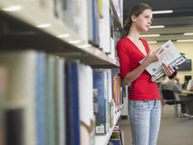 Thoughtful Girl Reading Books In Library Stock Photography