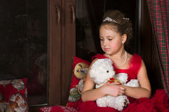 Thoughtful Girl in a red dress hugging a plush bear Royalty Free Stock Image
