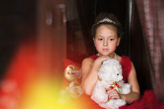 Thoughtful Girl in a red dress hugging a plush bear Stock Photo