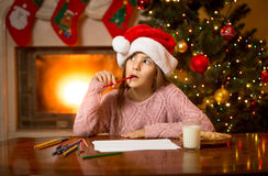 Thoughtful girl in Santa cap thinking of letter with gift wishes Royalty Free Stock Photography