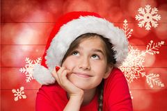Thoughtful girl in santa hat against digitally generated background Royalty Free Stock Photography
