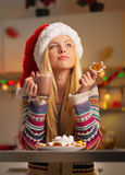 Thoughtful girl in santa hat with cookie Royalty Free Stock Image