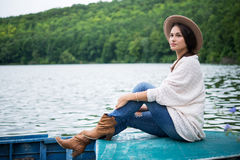 Thoughtful girl sits in a boat on a lake Stock Image