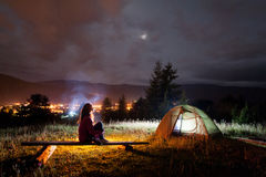 Thoughtful girl sitting on a bench near tent and campfire Royalty Free Stock Photo