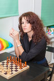 Thoughtful girl sitting at board with chess Royalty Free Stock Photos