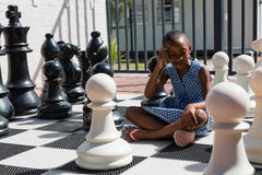 Thoughtful girl sitting by chess pieces Royalty Free Stock Photo