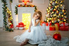 Thoughtful girl sitting in Christmas decorated room. Thoughtful cute little girl in white dress sitting in room decorated for Christmas Royalty Free Stock Photo