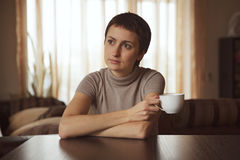 Thoughtful girl sitting with a cup of coffee Royalty Free Stock Images