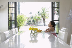 Thoughtful Girl Sitting At Dining Table Royalty Free Stock Photo