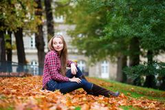 Thoughtful girl sitting on the ground at fall Stock Image
