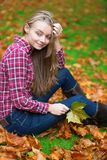 Thoughtful girl sitting on the ground at fall Royalty Free Stock Photos