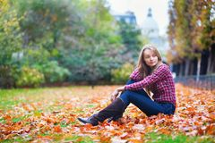Thoughtful girl sitting on the ground at fall Stock Photos