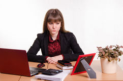 Thoughtful girl sitting at office desk Royalty Free Stock Photos