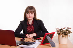 Thoughtful girl sitting at office desk Royalty Free Stock Photography