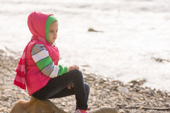Thoughtful girl sitting on a rock on stony beach of the sea and looks into the distance Stock Image