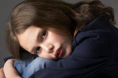 Thoughtful Girl Sitting In Studio Royalty Free Stock Image