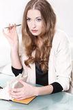 Thoughtful girl sitting at the table with notebook and. Pen Royalty Free Stock Image
