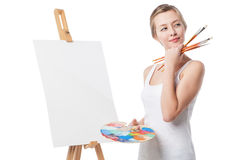 Thoughtful girl standing by canvas. Royalty Free Stock Photography