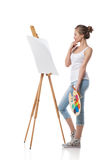 Thoughtful girl standing by canvas. Royalty Free Stock Images