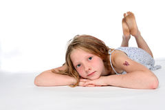 Thoughtful girl on stomach Royalty Free Stock Images
