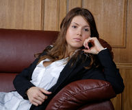 The thoughtful girl in  suit on a r sofa Royalty Free Stock Images