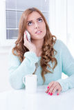 Thoughtful girl talking on the phone with cup of coffee Royalty Free Stock Image