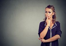 Thoughtful girl touching lips in doubts royalty free stock images