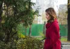 Thoughtful girl walking. Portrait of an attractive beautiful pretty cute young caucasian thoughtful woman (girl, female, person, model) in red coat walking Royalty Free Stock Images