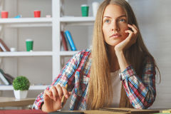 Thoughtful girl writing in notepad. Portrait of attractive thoughtful european girl doing writing in notepad at workplace. Paperwork concept Royalty Free Stock Images