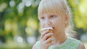 Thoughtful girl 6 years old is eating ice cream in the park. Holiday in summer and vacations. 4K 10 bit video stock video