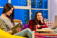 Thoughtful girls writing in notebook. Focus on two attractive pensive asian and caucasian females. They noting in dairies while sitting in apartment. Muse Royalty Free Stock Photography