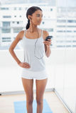 Thoughtful gorgeous model in sportswear listening to music Stock Photography