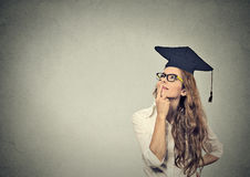 Thoughtful graduate graduated student young woman in cap gown looking up thinking