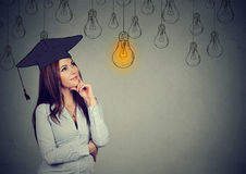 Thoughtful graduate student looking up at bright light bulb royalty free stock photography