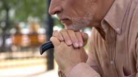 Thoughtful grandfather leaning walking stick, sitting in park alone, retirement stock image