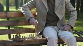 Thoughtful grandfather moving chess figures on board, playing alone in park. Stock footage stock video footage