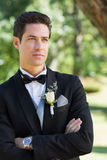 Thoughtful groom with arms crossed in garden Stock Photography