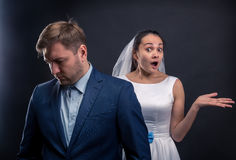 Thoughtful groom and surprised bride studio photo Stock Images