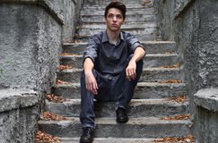 Thoughtful guy in gray sitting on gray stairs Stock Images
