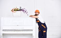 Thoughtful guy leaning on the top of vintage white piano with glass flower vase isolated on white background. Bearded. Worker enjoying short break stock photos