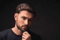 Thoughtful guy making serious decision. Young man is standing and looking at camera pensively. He is touching his chin. Isolated and copy space in right side Royalty Free Stock Photo