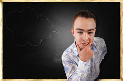 Thoughtful guy on school board background Royalty Free Stock Photos