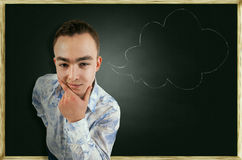 Thoughtful guy on school board background Royalty Free Stock Photography