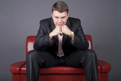 Thoughtful guy in a suit sitting on a red couch. Thoughtful young man in a suit sitting on a red couch Stock Photos