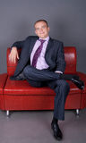 Thoughtful guy in a suit sitting on a red couch Royalty Free Stock Photos