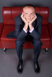 Thoughtful guy in a suit sitting on a red couch Stock Photos