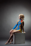 Thoughtful gymnast posing in colorful leotard Stock Photography
