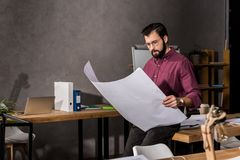 Thoughtful handsome architect looking at blueprint. In office stock photography