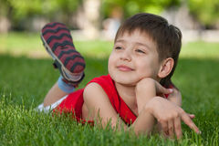 Thoughtful handsome boy on the green grass Stock Image