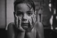A thoughtful handsome boy with water drops on her face. Black and white photo stock photos